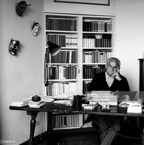 Italian writer Alberto Moravia sitting at the writing desk 1960s
