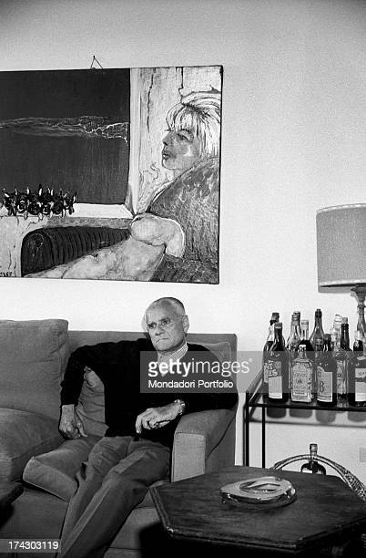 Italian writer Alberto Moravia sitting on a sofa in the living room 1960s