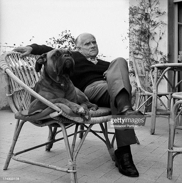 Italian writer Alberto Moravia sitting on the terrace in a wicker chair with a dog 1960s