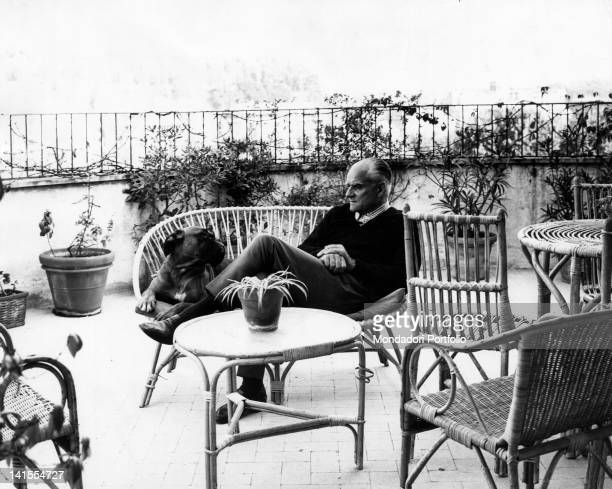 Italian writer Alberto Moravia sitting on the terrace of his home with his dog Rome 1968