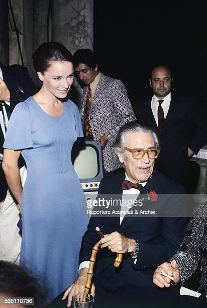 Italian writer and director Mario Soldati and TV host Aba Cercato attending a party 1974