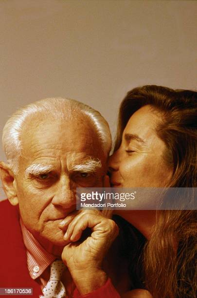 Italian writer and journalist Alberto Moravia being kissed by his Spanishborn Italian partner and writer Carmen Llera Rome 1984