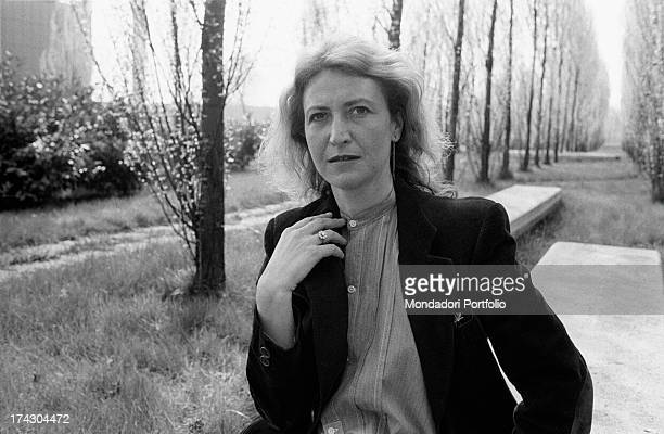 Italian writer and journalist Barbara Alberti sitting in a garden leaning her hand on her shoulder 1970s