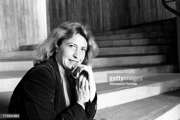 Italian writer and journalist Barbara Alberti smiling with her hand on her chin sitting on a staircase 1970s