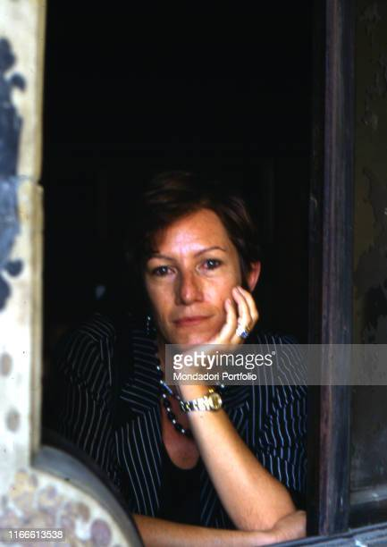 Italian writer and journalist Lidia Ravera looking out a window 1990s
