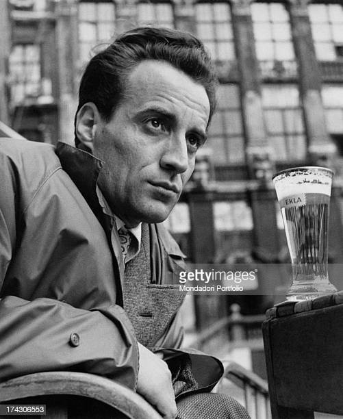 Italian writer and journalist Roberto De Monticelli sitting in front of a glass of beer 1960s