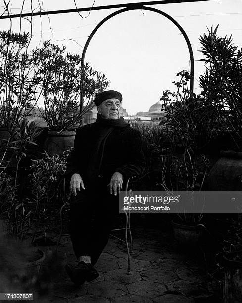 Italian writer and poet Aldo Palazzeschi sitting in an armchair leaning his head on his hand. Rome, 1963.