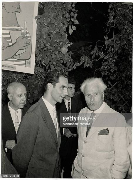 Italian writer and poet Piero Jahier talking with Italian journalist and writer Italo Calvino during the Viareggio Literary Prize Next to them...