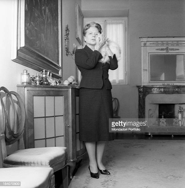 Italian writer and translator Anna Banti cuddles her white cat by the fireplace in her fashionable house in Florence embellished by many artworks...
