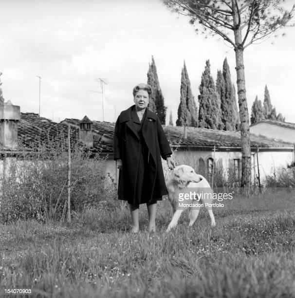 Italian writer and translator Anna Banti photographed in the exterior of her fashionable house in Florence while plays with her dog Florence June 1962