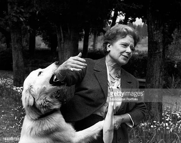 Italian writer and translator Anna Banti playing with her dog 1960s
