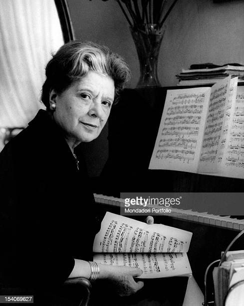 Italian writer and translator Anna Banti sitting at the piano holding a piano score 1960s