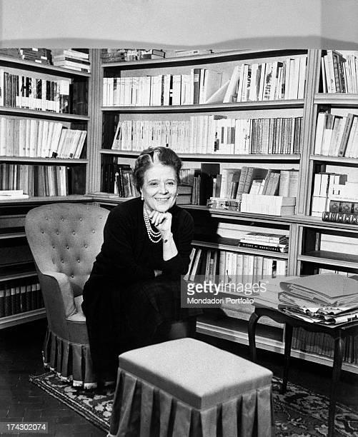 Italian writer Anna Banti smiling sitting among her books 1960s