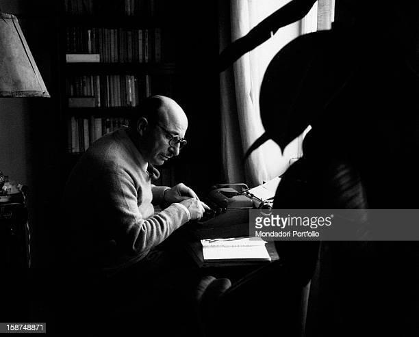Italian writer Carlo Bernari sitting at the desk and typing. 1964