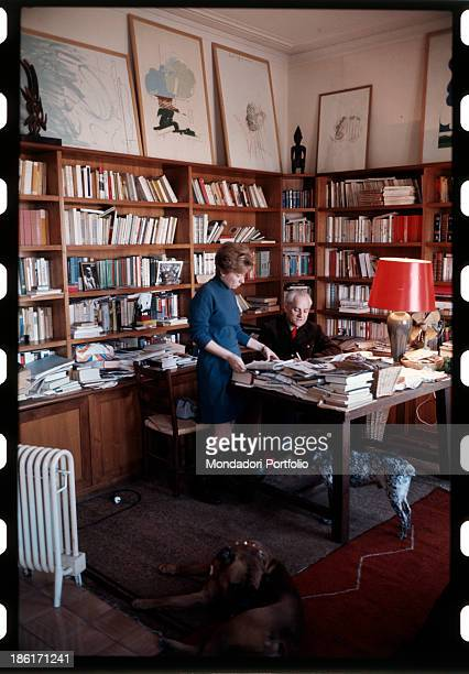 Italian writer Dacia Mariani reading something beside her partner the Italian writer Alberto Moravia in their study at home Beside her a bookcase and...