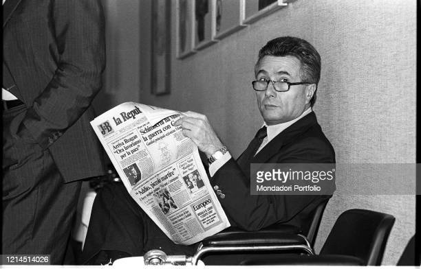 Italian writer journalist poet theater critic and politician Alberto Arbasino reads the newspaper sitting on an armchair Rome October 14th 1987
