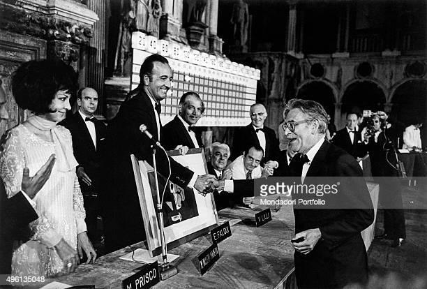 Italian writer Mario Soldati winner of the Premio Campiello with the novel L'attore shaking hands with Italian lawyer Mario Valeri Manera holding a...