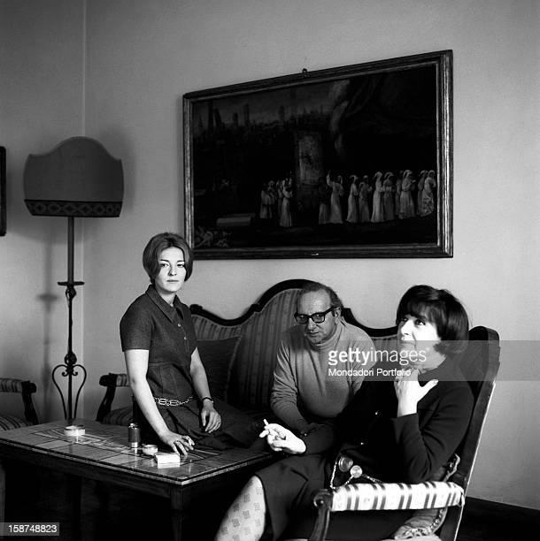 Italian writer Vasco Pratolini at home sitting on a sofa with his wife Cecilia Punzo and his daughter Aurelia Rome 1969