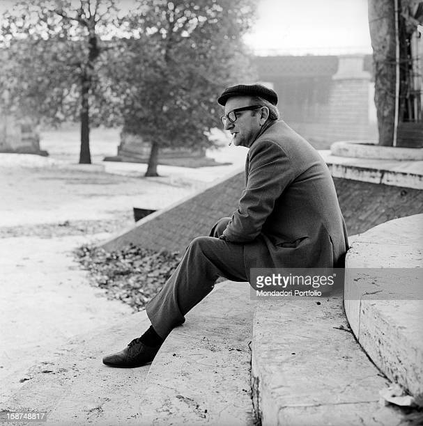 Italian writer Vasco Pratolini sitting on a step on the Tiber Island and smoking a cigarette. Rome, 1969