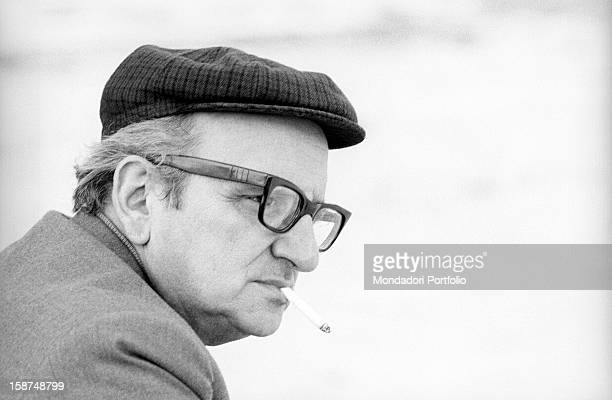 Italian writer Vasco Pratolini smoking a cigarette on the Tiber Island. Rome, 1969