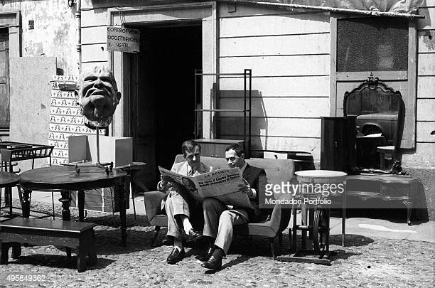 Italian writers Carlo Fruttero and Franco Lucentini reading the newspaper sitting on the sofa at a secondhand dealer's shop beside a sculpture...