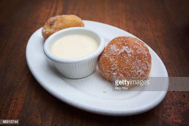 italian zeppole with cream dipping sauce - zeppole foto e immagini stock