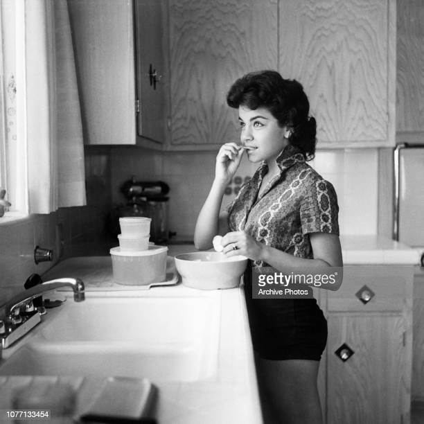 ItalianAmerican actress and singer Annette Funicello eating crisps in the kitchen circa 1960