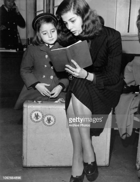 Italianborn actress Pier Angeli reads to her little sister Patricia at New York International Airport USA December 1952 They have just arrived from...