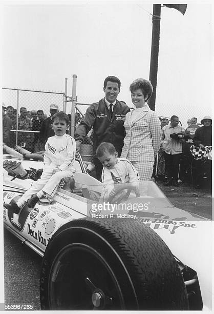Italianborn American race car driver Mario Andretti and his wife Dee Ann stand with his sons Mike and Jeff perched on his car May 1967