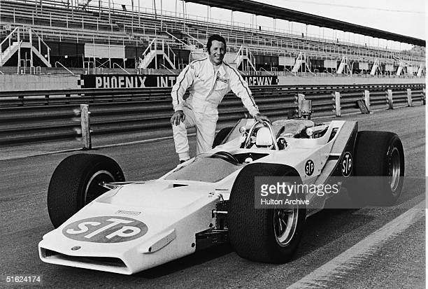 Italian-born American racecar driver Mario Andretti poses in a jumpsuit with his new STP-McNamara car seen still without paint during first run-in...