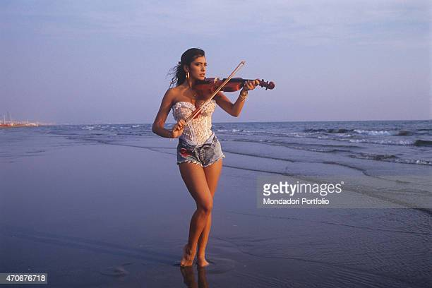 Italianborn British singer and showgirl Sabrina Salerno playing violin by the sea wearing a lace bodysuit 1988