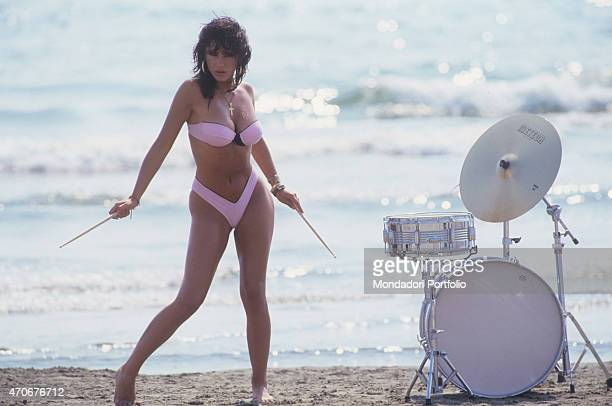 Italianborn British singer and showgirl Sabrina Salerno posing in bikini beside a drum 1988