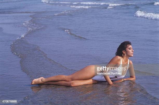 Italianborn British singer and showgirl Sabrina Salerno posing in swimsuit lying by the sea 1988