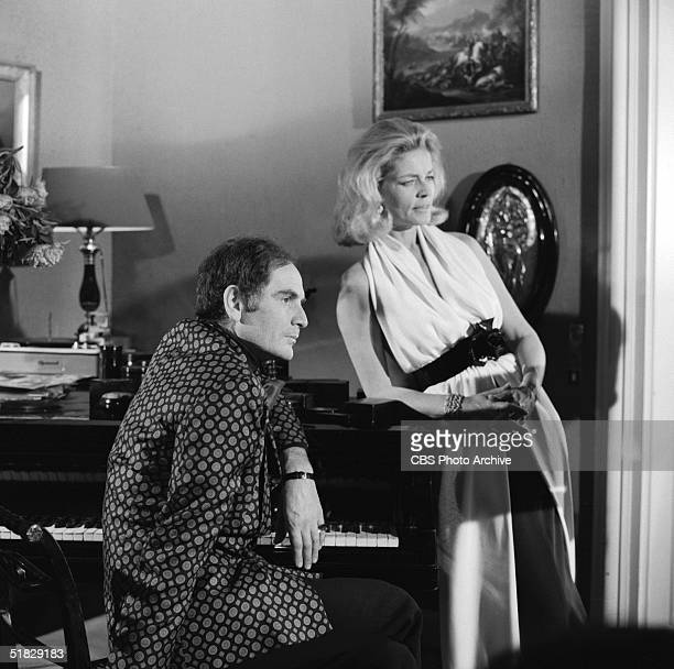 Italianborn fashion designer Pierre Cardin and American actress Lauren Bacall pose near a piano for the CBS special 'The Paris Collections Fall...