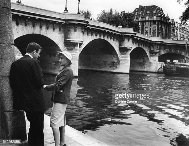 Italianborn French actor and singer Yves Montand and his wife French actress Simone Signoret in front of the Pont Neuf accross the river Seine in...