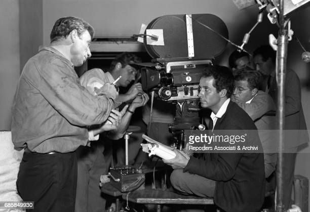 Italianborn French actor Yves Montand talking to Italian director Gillo Pontecorvo during a break on the set of The Wide Blue Road Italy 1957