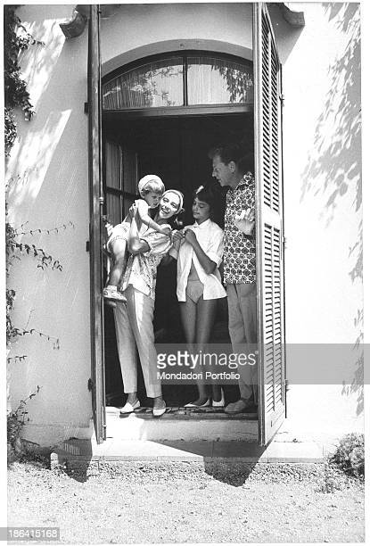 Italianborn French actress Marisa Pavan with her son JeanClaude Aumont in her arms smiling with French actor JeanPierre Aumont and Tina Aumont...