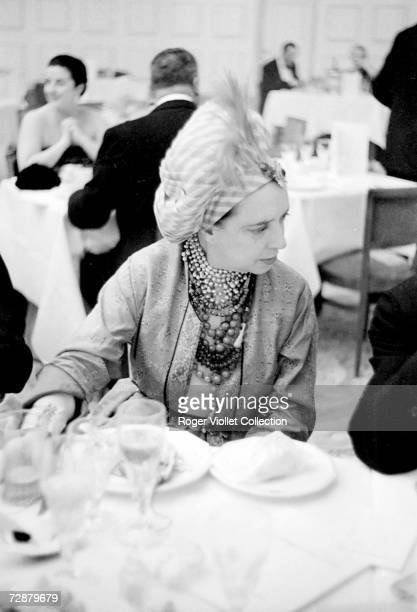 Italianborn French fashion designer Elsa Schiaparelli wears a turban with a single feather as she sits at a dinner table at a formal occasion 1940
