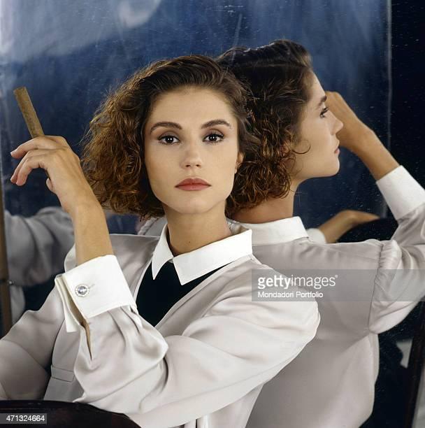 Italianborn French showgirl Alessandra Martines posing holding a cigar 1989