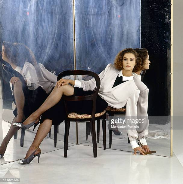 Italianborn French showgirl Alessandra Martines posing seated on a chair 1989