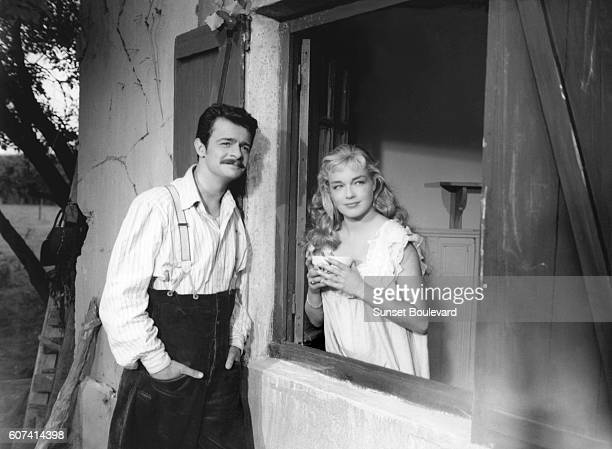 Italianborn French singer and actor Serge Reggiani and French actress Simone Signoret on the set of Casque d'Or written and directed by Jacques Becker
