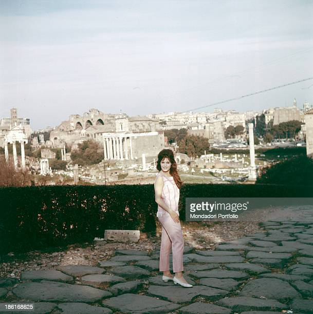 Italianborn French singer Dalida posing on a Roman paved road Behind her the Imperial Fora Rome 1950s