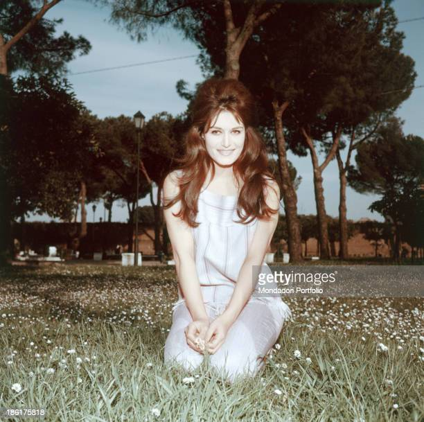 Italian-born French singer Dalida smiling on a lawn of daisies at the Imperial Fora. Rome, 1950s.