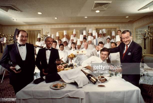 Italianborn restaurateur Sirio Maccioni with staff at Le Cirque his establishment in New York 1990 Maccioni is holding a large carving knife over...