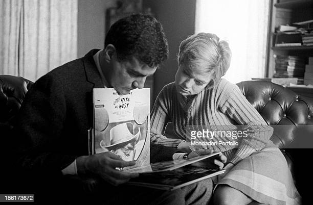 Italianborn Swiss singer and actress Rita Pavone and her husband and Italian singer Teddy Reno watching some records covers 1968