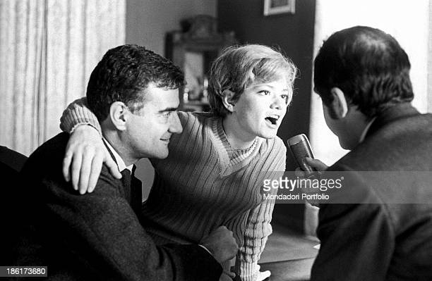 Italianborn Swiss singer and actress Rita Pavone speaking into the microphone of a reporter Her husband and Italian singer Teddy Reno looking at her...