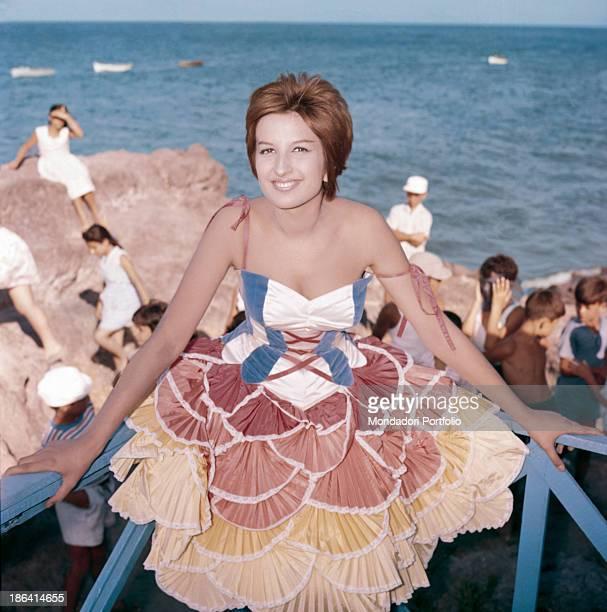 Italianborn Swiss singer Mina singing at the beach wearing a frilled dress 1959