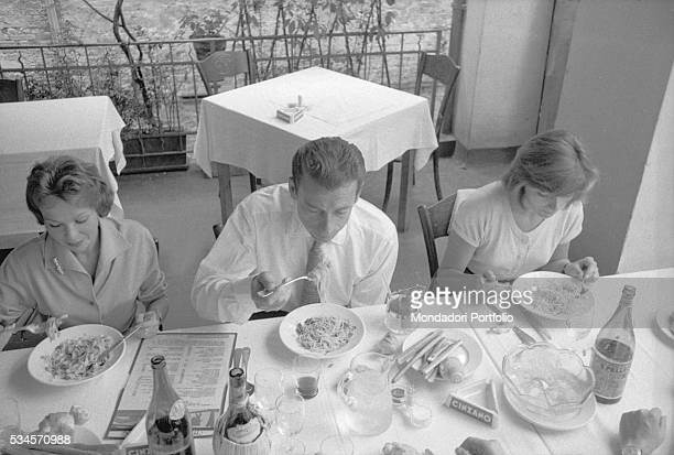 ItalianFrench singer and actor Yves Montand and French actresses Francoise Arnoul and Anouk Aimée sitting at the restaurant during the XVI Venice...