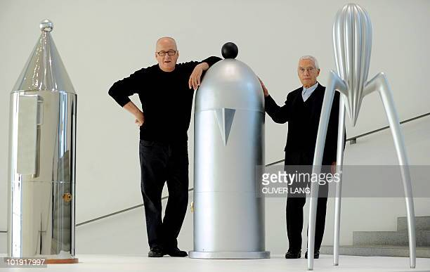 Italians Alberto Alessi owner of the kitchen utensil company Alessi and designer Alessandro Mendini pose between giant mockups of their kitchen...