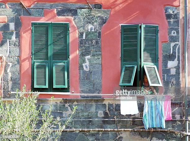 Italien, Ligurien, Cinque Terre, Vernazza: Frau haengt Waesche zum Trocknen aus dem Fenster auf die Waescheleine